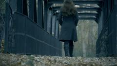Beautiful woman walking away from camera low angle over bridge Stock Footage