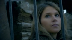Beautiful woman contemplative close up, tracked iron bars in foreground Stock Footage
