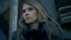 Beautiful woman's face low angle tracked shot old building in bckground - stock footage