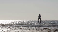 A silhouette outline of a lady paddleboarding in the sea Stock Footage