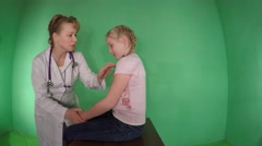 Beautiful female pediatrician treats a little girl-blonde. - stock footage