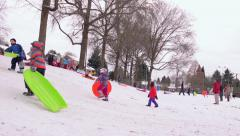 Kids gather at the park on a snow day for some sledding - stock footage