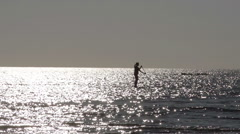 A silhouette outline of a lady paddleboarding in the sea - stock footage