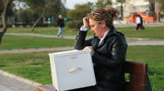 A fired businesswoman with a box of personal items Stock Footage