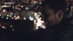 Portrait of a handsome young Latino man looking out over city lights at night Stock Footage