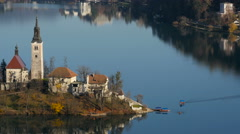 Boat and pletnas on the shore of the island with Pilgrimage Church in Bled Stock Footage