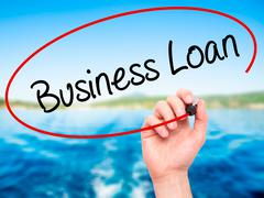 Man Hand writing Business Loan with black marker on visual screen Stock Photos