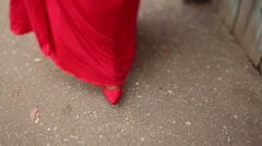 The girl in the red dress and scarlet shoes sweeping the road Stock Footage