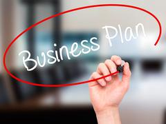 Man Hand writing  Business Plan with black marker on visual screen Stock Photos