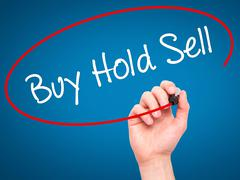 Man Hand writing  Buy Hold Sell with black marker on visual screen - stock photo