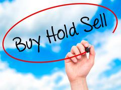 Man Hand writing  Buy Hold Sell with black marker on visual screen Stock Photos