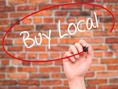 Man Hand writing Buy Local  with black marker on visual screen - stock photo