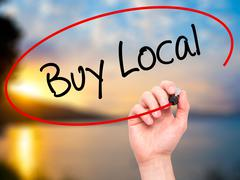 Stock Photo of Man Hand writing Buy Local  with black marker on visual screen