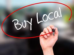 Man Hand writing Buy Local  with black marker on visual screen Stock Photos