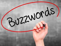 Man Hand writing Buzzwords with black marker on visual screen - stock photo