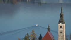 View of a boat sailing on Lake Bled and the tower of Pilgrimage Church in Bled - stock footage
