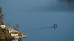 View of a pletna sailing from the island on Lake Bled Stock Footage