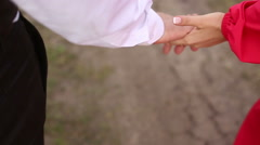 Modern girl and a stylish young man hold hands and walk down the path Stock Footage