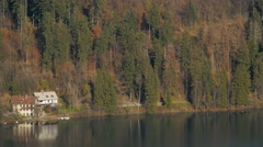View of two buildings and the forest on a sunny autumn day in Bled Stock Footage