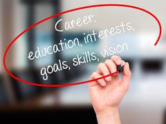 Man Hand writing Career: education, interests, goals, skills, vision with bla - stock photo