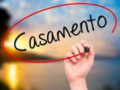 Man Hand writing Casamento (Wedding in Portuguese) with black marker on visua - stock photo