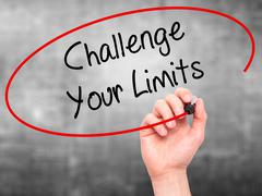Man Hand writing Challenge Your Limits with black marker on visual screen - stock photo