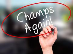 Man Hand writing Champs Again with black marker on visual screen - stock photo