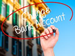 Man Hand writing Change Bank Account with black marker on visual screen - stock photo