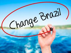 Stock Photo of Man Hand writing Change Brazil  with black marker on visual screen