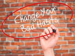 Man Hand writing Change Your Bad Habits  with black marker on visual screen - stock photo