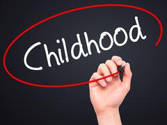 Man Hand writing Childhood with black marker on visual screen - stock photo