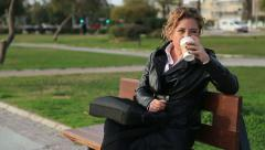 Business woman on break drinking coffee in a park Stock Footage