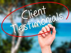 Man Hand writing Client Testimonials with black marker on visual screen Stock Photos
