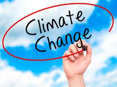 Man Hand writing Climate Change with black marker on visual screen Stock Photos