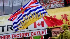 Smiling woman waving flags of China and Canadian British Columbia Stock Footage