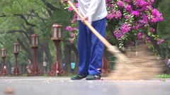 A worker sweeping the streets in a park in Beijing Stock Footage