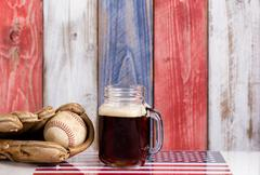 Front view of a glass of cold dark beer with a worn baseball mitt and ball. Stock Photos