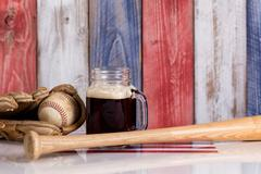 Front view of a glass of cold dark beer with a worn baseball mitt, bat and ba - stock photo