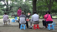 Mini performance in public park Beijing, Chinese woman, small audience, seniors Stock Footage