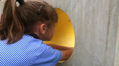Little girl goes through a hole in the wall Stock Footage