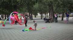 Children and seniors play with ribbons in a park in Beijing, China Stock Footage