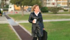Business woman on lunch break in city park drinking coffee Stock Footage