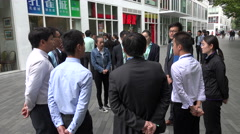 Chinese manager talks to office workers of a real estate company in Beijing Stock Footage