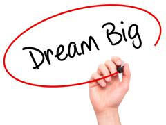 Man Hand writing Dream Big  with black marker on visual screen Stock Photos