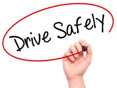 Man Hand writing  Drive Safely with black marker on visual screen - stock photo