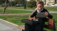 Business woman using tablet on lunch break in city park Stock Footage