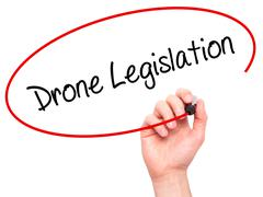 Man Hand writing Drone Legislation with black marker on visual screen Stock Photos