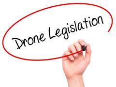 Man Hand writing Drone Legislation with black marker on visual screen - stock photo