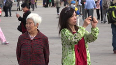Woman takes a photo of Tiananmen Square with smartphone, Beijing, China Stock Footage