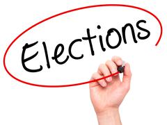 Man Hand writing Elections with black marker on visual screen - stock photo